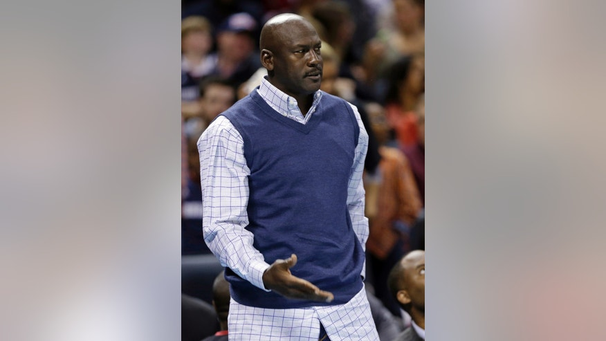 Charlotte Bobcats owner Michael Jordan complains about a call during the first half of an NBA basketball game against the Phoenix Suns in Charlotte, N.C., Friday, Nov. 22, 2013. (AP Photo/Chuck Burton)