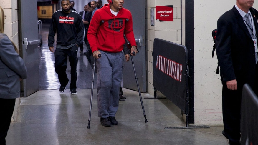 In this photo taken on Friday, Nov. 22, 2013,  Chicago Bulls point guard Derrick Rose (1) leaves the Moda Center on crutches after he was injured in an NBA basketball game against the Portland Trail Blazers in Portland, Ore. (AP Photo/The Oregonian, Bruce Ely )  MAGS OUT; TV OUT; LOCAL TV OUT; LOCAL INTERNET OUT; THE MERCURY OUT; WILLAMETTE WEEK OUT; PAMPLIN MEDIA GROUP OUT