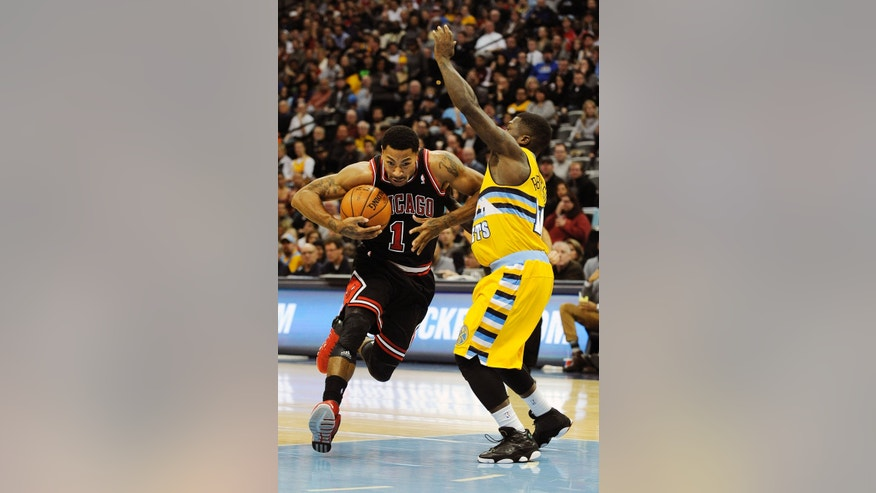 Chicago Bulls point guard Derrick Rose, left, drives against Denver Nuggets point guard Nate Robinson, right, in the first quarter of an NBA basketball game on Thursday, Nov. 21, 2013, in Denver. (AP Photo/Chris Schneider)