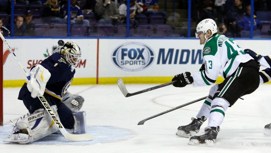 St. Louis Blues goalie Brian Elliott, left, deflects a shot from Dallas Stars' Valeri Nichushkin, of Russia, during the first period of an NHL hockey game Saturday, Nov. 23, 2013, in St. Louis. (AP Photo/Jeff Roberson)