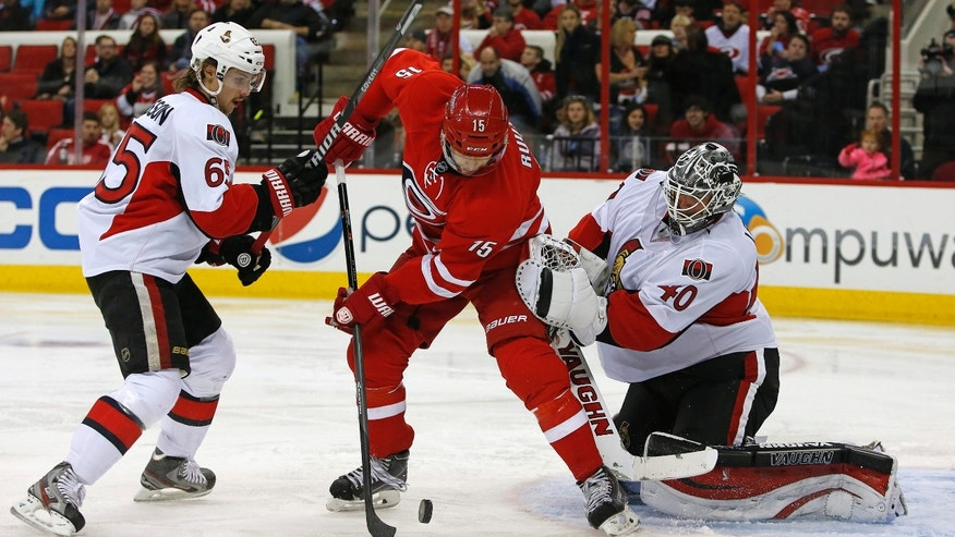 Carolina Hurricanes' Tuomo Ruutu (15), of Finland, battles between Ottawa Senators goalie Robin Lehner (40) and Erik Karlsson (65) during the second period of an NHL hockey game in Raleigh , N.C., Sunday, Nov. 24, 2013. (AP Photo/Karl B DeBlaker)