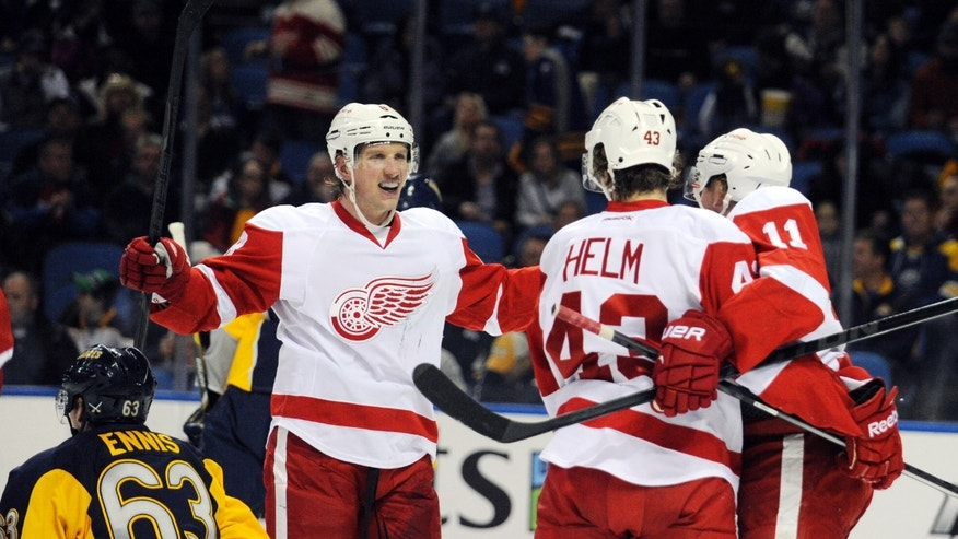 Buffalo Sabres' Tyler Ennis (63) passes a celebration by Detroit Red Wings' Justin Abdelkader (8), Darren Helm (43) and Daniel Alfredsson (11) after Helm scored  during the second period of an NHL hockey game in Buffalo, N.Y., Sunday, Nov. 24, 2013. (AP Photo/Gary Wiepert)