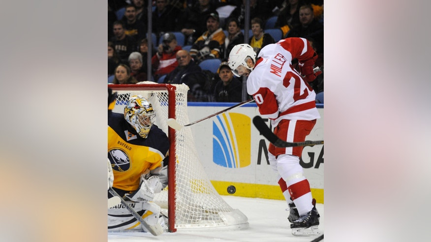 Buffalo Sabres goaltender Ryan Miller (30) keeps an eye on his brother, Detroit Red Wings left winger Drew Miller (20), as he moves the puck behind the goal during the second period of an NHL hockey game in Buffalo, N.Y., Sunday, Nov. 24, 2013. (AP Photo/Gary Wiepert)