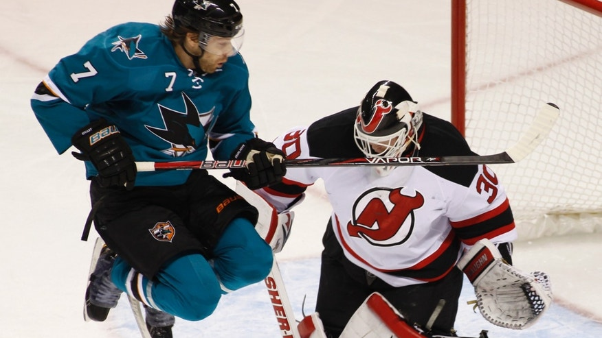 San Jose Sharks' Brad Stuart, left, jumps up in front of New Jersey Devils goalie Martin Brodeur during the first period of an NHL hockey game on Saturday, Nov. 23, 2013, in San Jose, Calif. (AP Photo/George Nikitin)