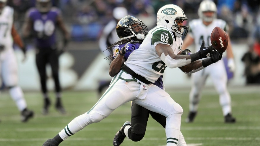 New York Jets tight end Jeff Cumberland attempts to gain control of the ball under pressure from Baltimore Ravens cornerback Lardarius Webb during the second half of an NFL football game in Baltimore, Sunday, Nov. 24, 2013. (AP Photo/Gail Burton)
