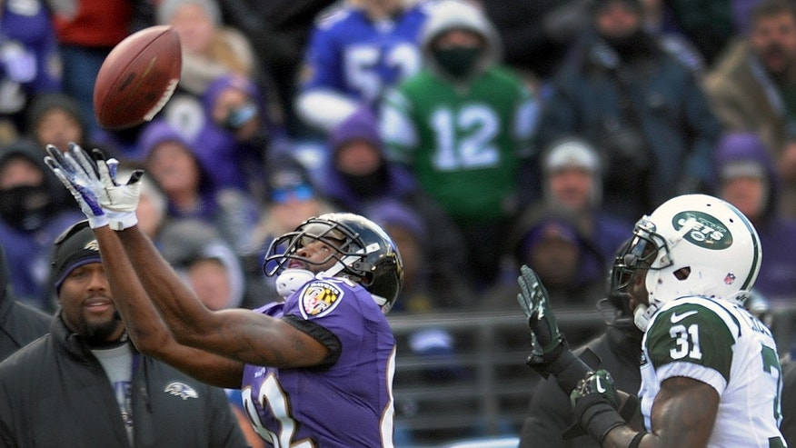 Baltimore Ravens wide receiver Torrey Smith pulls in a pass under pressure from New York Jets cornerback Antonio Cromartie, right, during the first half of an NFL football game in Baltimore, Md., Sunday, Nov. 24, 2013. (AP Photo/Gail Burton)