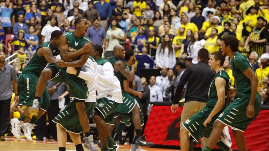 Charlotte's players celebrate winning the NCAA college basketball Puerto Rico Tip-off tournament following their victory over Michigan in San Juan, Puerto Rico, Sunday, Nov. 24, 2013. (AP Photo/Ricardo Arduengo)