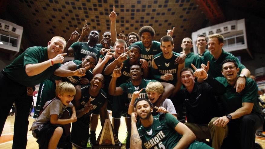 Charlotte's players celebrate with their trophy after winning the NCAA college basketball Puerto Rico Tip-off tournament following their victory over Michigan in San Juan, Puerto Rico, Sunday, Nov. 24, 2013. (AP Photo/Ricardo Arduengo)