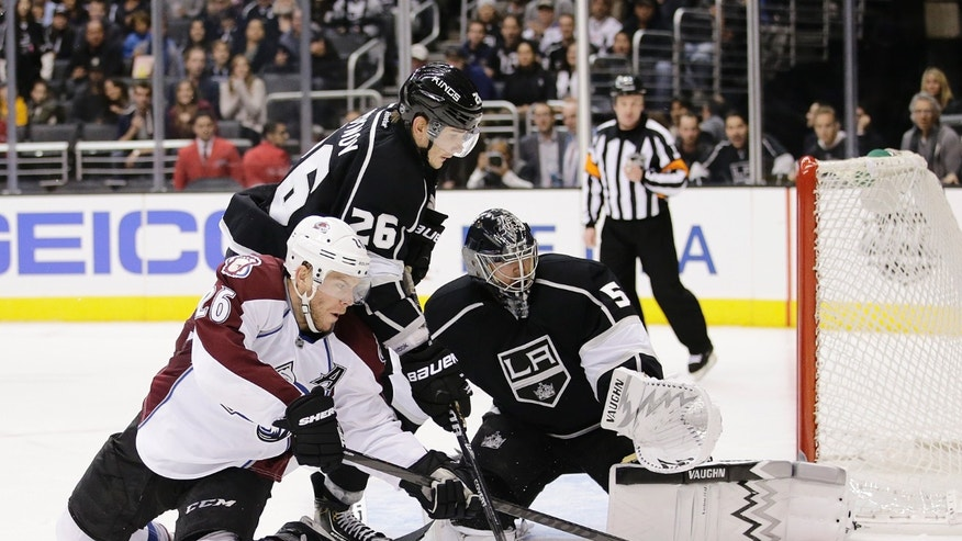 Los Angeles Kings' Slava Voynov, top, of Russia, and Colorado Avalanche's Paul Stastny go after the puck as Los Angeles Kings goalie Ben Scrivens, right, looks on during the third period of an NHL hockey game on Saturday, Nov. 23, 2013, in Los Angeles. The Avalanche won 1-0 in overtime. (AP Photo/Jae C. Hong)