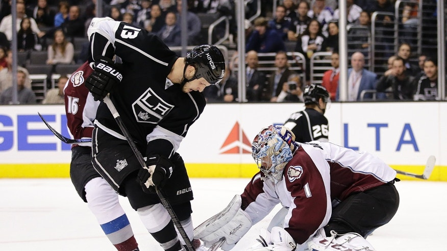 Colorado Avalanche goalie Semyon Varlamov, right, of Russia, makes a save in front of Los Angeles Kings' Kyle Clifford during the second period of an NHL hockey game on Saturday, Nov. 23, 2013, in Los Angeles.(AP Photo/Jae C. Hong)