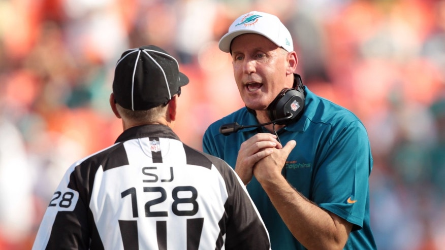 Miami Dolphins head coach Joe Philbin, right, speaks to side judge Larry Rose during the first half of an NFL football game against the Carolina Panthers, Sunday, Nov. 24, 2013, in Miami Gardens, Fla. (AP Photo/J Pat Carter)