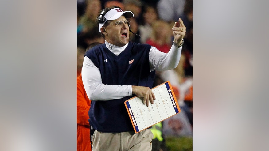 ADVANCE FOR WEEKEND EDITIONS, NOV. 23-24 - FILE - In this Oct. 26, 2013 file photo, Auburn head coach Gus Malzahn reacts to a play during the first half of an NCAA college football game against Florida Atlantic in Auburn, Ala. No. 6 Auburn's first-year coach has outdone himself this season, taking a down-and-out program back into Southeastern Conference and perhaps national title contention with his no-huddle offense and his unflappable focus. (AP Photo/Butch Dill, File)