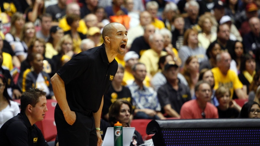 VCU head basketball coach Shaka Smart yells instructions out to his players during the first half of an NCAA college basketball game against Georgetown in San Juan, Puerto Rico, Sunday, Nov. 24, 2013. (AP Photo/Ricardo Arduengo)