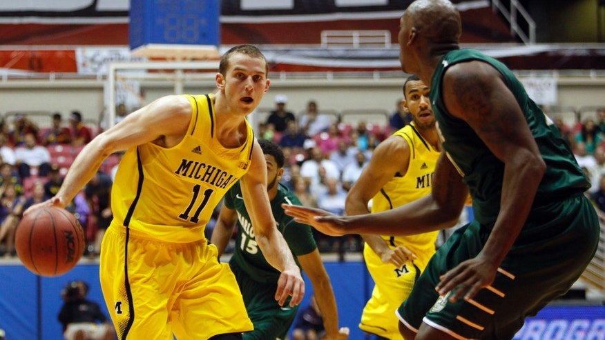 Charlotte forward Willie Clayton, right, pressures Michigan guard Nik Stauskas during a NCAA college basketball game in San Juan, Puerto Rico, Sunday, Nov. 24, 2013. (AP Photo/Ricardo Arduengo)