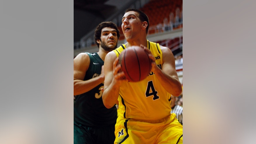 Michigan forward Mitch Gary (4) goes to the basket as Charlotte forward Marcus Bryan looks on at a NCAA college basketball game in San Juan, Puerto Rico, Sunday, Nov. 24, 2013. (AP Photo/Ricardo Arduengo)