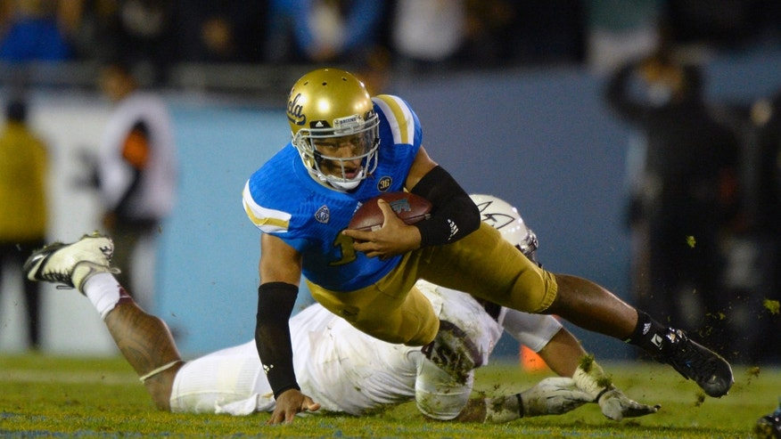 UCLA quarterback Brett Hundley, left, is tackled by Arizona State linebacker Chris Young during the second half an NCAA college football game, Saturday, Nov. 23, 2013, in Pasadena, Calif. (AP Photo/Mark J. Terrill)