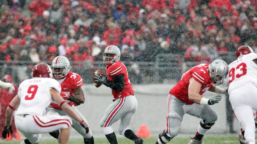 Ohio State quarterback Braxton Miller, center, drops back to pass in the swirling snow against Indiana during the first quarter of an NCAA college football game Saturday, Nov. 23, 2013, in Columbus, Ohio. (AP Photo/Jay LaPrete)