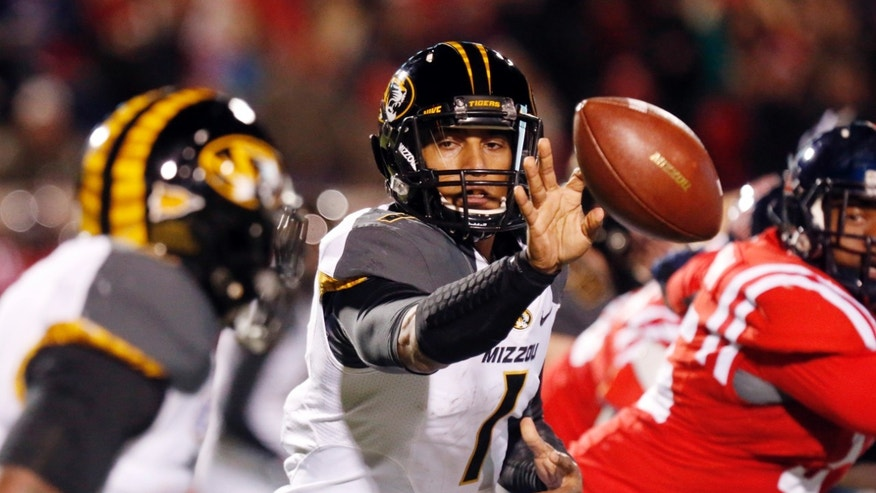 Missouri quarterback James Franklin (1) pitches out to Missouri running back Marcus Murphy for short yards against Mississippi during the first half of an NCAA college football game Saturday, Nov. 23, 2013, in Oxford, Miss. (AP Photo/Rogelio V. Solis)
