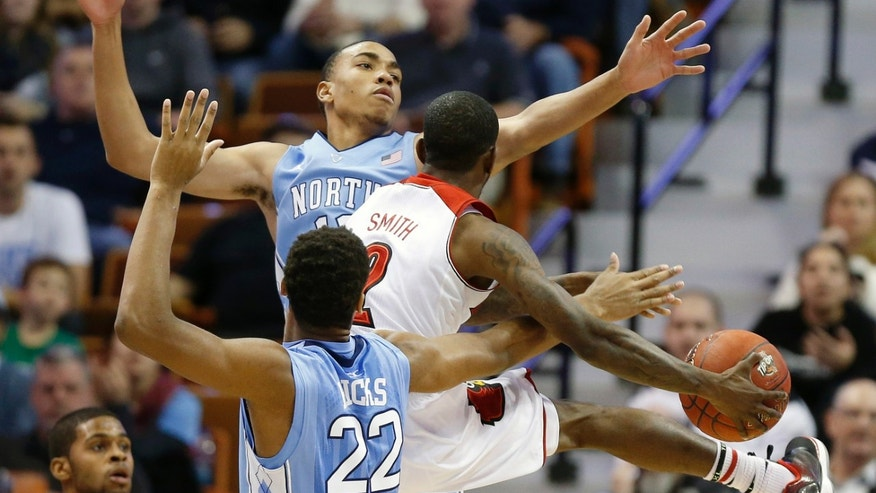 Louisville's Russ Smith (2) goes up to shoot against North Carolina's Brice Johnson (11) and Isaiah Hicks (22) during the first half of an NCAA college basketball game in the Basketball Hall of Fame Tip-Off tournament championship in Uncasville, Conn., Sunday, Nov. 24, 2013. (AP Photo/Michael Dwyer)
