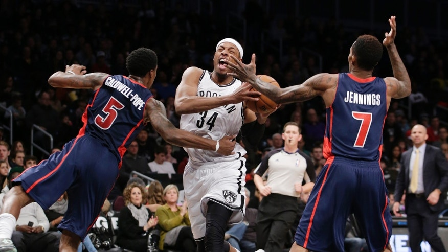 Detroit Pistons guard Kentavious Caldwell-Pope (5) fouls Brooklyn Nets forward Paul Pierce (34) as Detroit Pistons guard Brandon Jennings (7) defends in the first half of an NBA basketball game, Sunday, Nov. 24, 2013, in New York. (AP Photo/Kathy Willens)