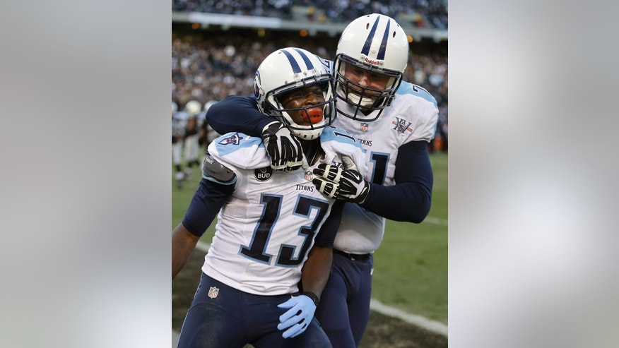 Tennessee Titans wide receiver Kendall Wright (13) celebrates with tackle Michael Roos after scoring on a 10-yard touchdown pass against the Oakland Raiders during the fourth quarter of an NFL football game in Oakland, Calif., Sunday, Nov. 24, 2013. The Titans won 23-19. (AP Photo/Ben Margot)
