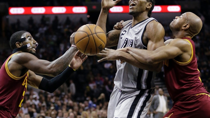 CORRECTS ORDER OF SPURS PLAYERS  - San Antonio Spurs' Kawhi Leonard, center, is fouled by Cleveland Cavaliers' Jarrett Jack, right, as Kyrie Irving, left, helps defend the play during the first half of an NBA basketball game Saturday, Nov. 23, 2013, in San Antonio. (AP Photo/Eric Gay)