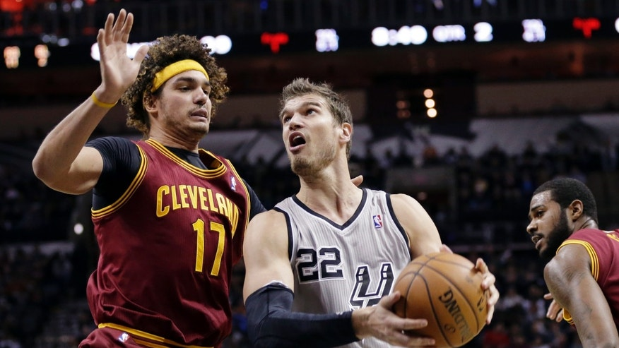 San Antonio Spurs' Tiago Splitter (22), of Brazil, works the ball around Cleveland Cavaliers' Anderson Varejao (17) during the first half of an NBA basketball game Saturday, Nov. 23, 2013, in San Antonio. (AP Photo/Eric Gay)