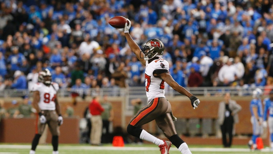 Tampa Bay Buccaneers cornerback Johnthan Banks (27) runs back to the sidelines after intercepting a pass intended for Detroit Lions wide receiver Calvin Johnson (81) during the fourth quarter of an NFL football game in Detroit, Sunday, Nov. 24, 2013. (AP Photo/Paul Sancya)