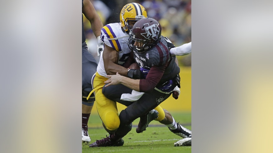 Texas A&M quarterback Johnny Manziel (2) is tackled by LSU defensive end Danielle Hunter (94) in the first half of an NCAA college football game in Baton Rouge, La., Saturday, Nov. 23, 2013. (AP Photo/Gerald Herbert)