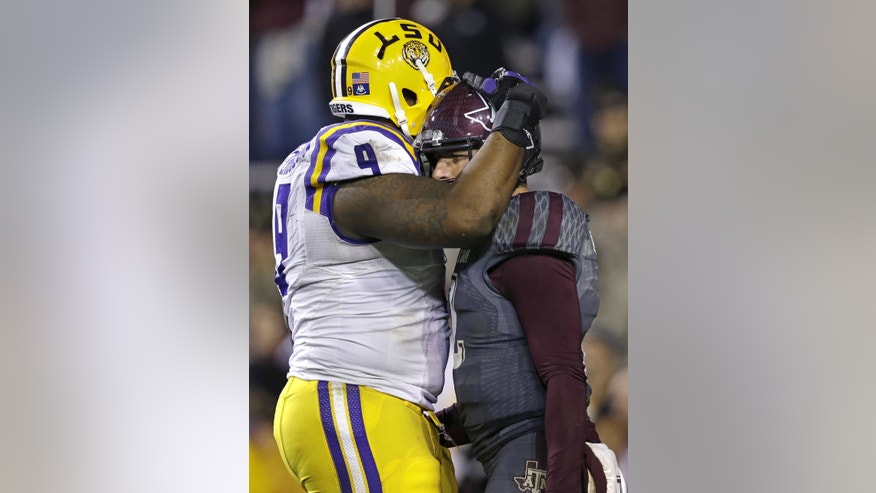 LSU defensive tackle Ego Ferguson (9) hugs Texas A&M quarterback Johnny Manziel late in the fourth quarter of an NCAA college football game in Baton Rouge, La., Saturday, Nov. 23, 2013. LSU won 34-10. (AP Photo/Gerald Herbert)