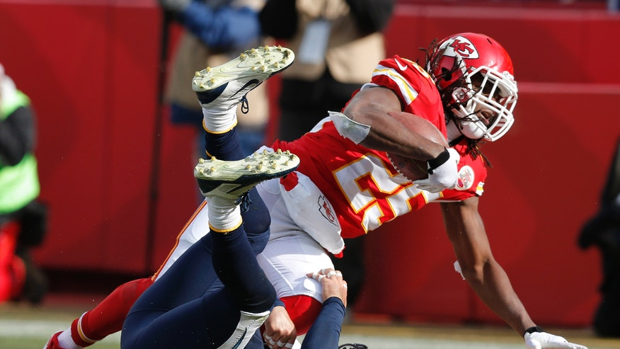 Kansas City Chiefs running back Jamaal Charles (25) scores a touchdown over San Diego Chargers free safety Eric Weddle during the first half of an NFL football game at Arrowhead Stadium in Kansas City, Mo., Sunday, Nov. 24, 2013. (AP Photo/Ed Zurga)