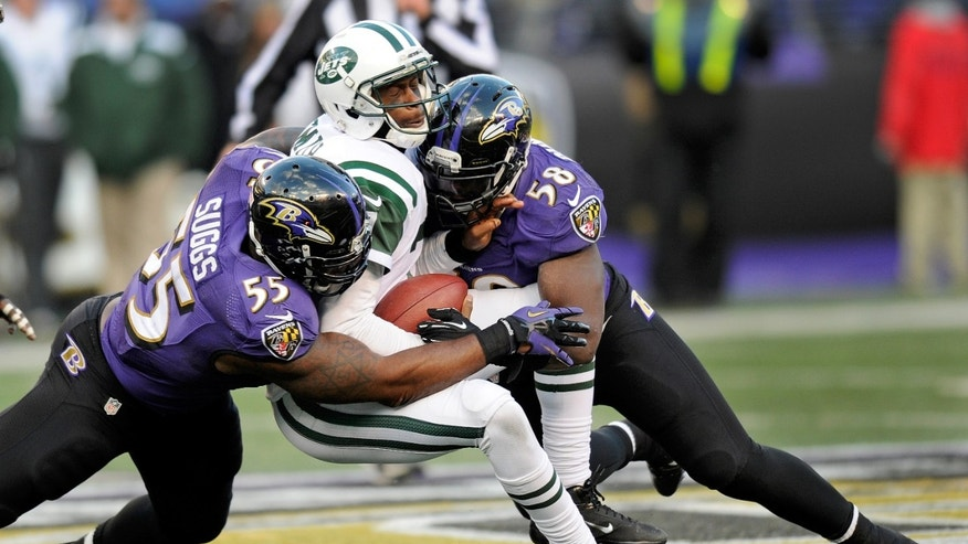 New York Jets quarterback Geno Smith, center, is tackled by Baltimore Ravens outside linebacker Terrell Suggs, left, and outside linebacker Elvis Dumervil, right, during the second half of an NFL football game in Baltimore, Sunday, Nov. 24, 2013. The Ravens won 19-3. (AP Photo/Nick Wass)