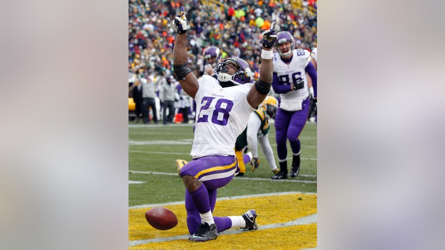 Minnesota Vikings' Adrian Peterson celebrates after rushing for a touchdown during the first half of an NFL football game against the Green Bay Packers Sunday, Nov. 24, 2013, in Green Bay, Wis. (AP Photo/Mike Roemer)