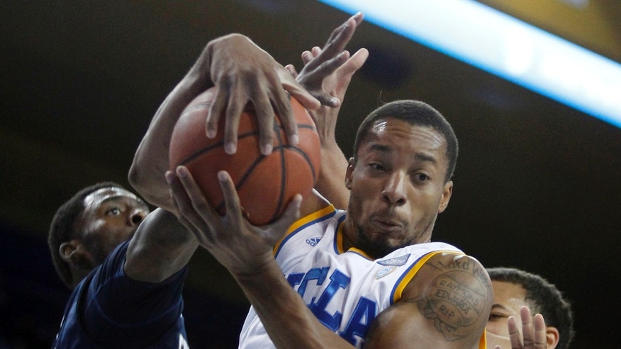 UCLA guard Norman Powell, center, pulls down a rebound against Chattanooga guard Casey Jones, left and UCLA guard Kyle Anderson, right, in the first half of their NCAA college basketball game Sunday, Nov. 24, 2013, in Los Angeles. (AP Photo/Alex Gallardo)
