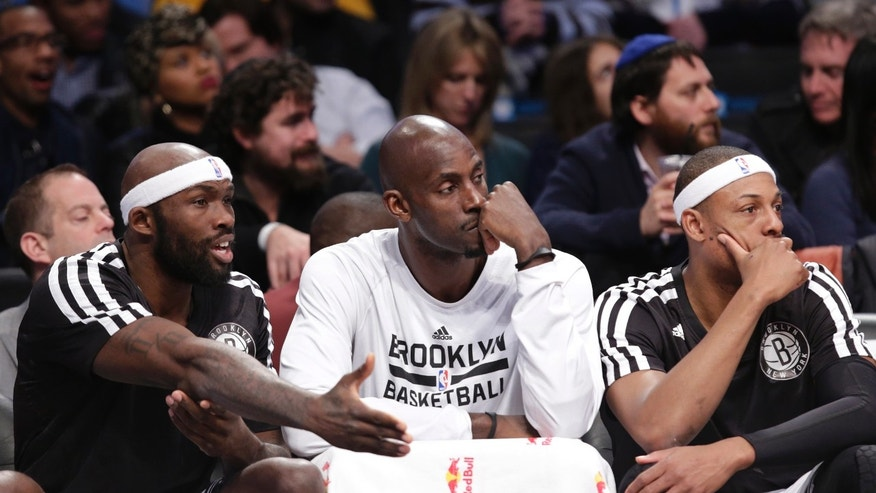 Brooklyn Nets center Andray Blatche, left, talks to teammates Kevin Garnett (2) and Paul Pierce, right, as the trio sit on the bench during the second half of an NBA basketball game against the Detroit Pistons, Sunday, Nov. 24, 2013, in New York. The Piston won 109-97. (AP Photo/Kathy Willens)