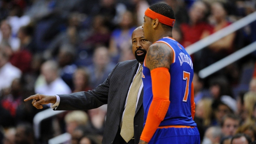 New York Knicks head coach Mike Woodson, left, talks with Carmelo Anthony during the first half of an NBA basketball game against the Washington Wizards, Saturday, Nov. 23, 2013, in Washington. (AP Photo/Nick Wass)