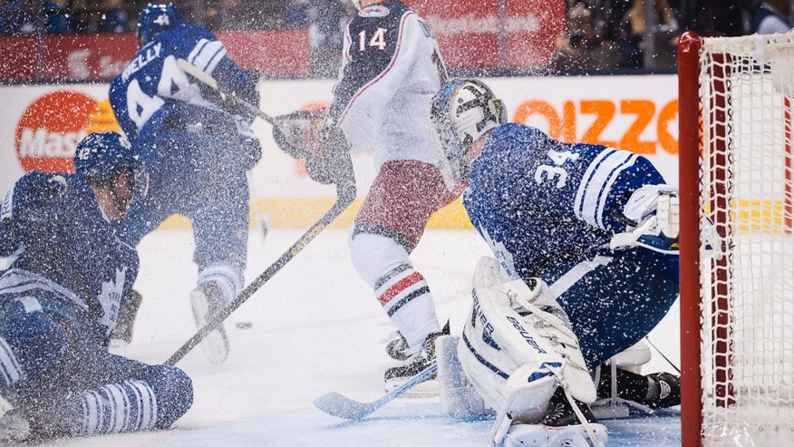 Toronto Maple Leafs goalie James Reimer is covered in spray after clearing the puck against the Columbus Blue Jackets during the first period of an NHL hockey game in Toronto on Monday, Nov. 25, 2013. (AP Photo/The Canadian Press, Aaron Vincent Elkaim)
