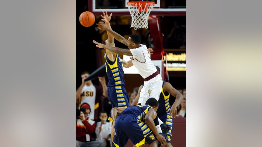 Arizona State guard Jahii Carson passes around Marquette guard Juan Anderson, left, during the first half of an NCAA basketball game, Monday, Nov. 25, 2013, in Tempe, Ariz. (AP Photo/Matt York)