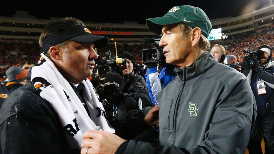 Oklahoma State head coach Mike Gundy, left, and Baylor head coach Art Briles, right, shake hands after their NCAA college football game in Stillwater, Okla., Saturday, Nov. 23, 2013. Oklahoma State won 49-17. (AP Photo/Sue Ogrocki)
