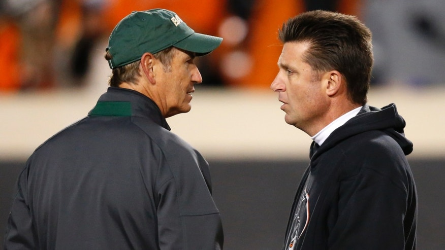 Baylor head coach Art Briles, left, and Oklahoma State head coach Mike Gundy, right, talk before the start of their NCAA college football game in Stillwater, Okla., Saturday, Nov. 23, 2013. (AP Photo/Sue Ogrocki)