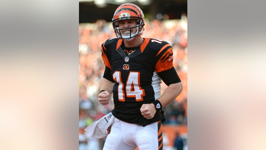 FILE - In this Nov. 4, 2012 file photo, Cincinnati Bengals quarterback Andy Dalton celebrates after the Bengals scored a touchdown against the Denver Broncos in the second half of an NFL football game in Cincinnati. The Bengals' Andy Dalton completes a tipped, 51-yard pass for a tying touchdown on the final play of regulation against the Ravens. A week later, another stunner _ a 73-yard TD by Auburn in college football. The reason these plays are such big deals is this: Desperation passes so rarely succeed. (AP Photo/Michael Keating, File)