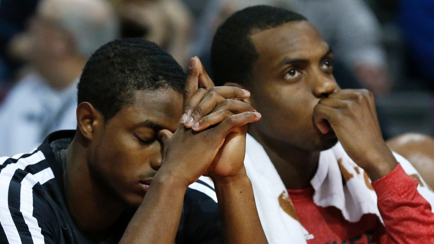 Milwaukee Bucks guard Brandon Knight, left, and Milwaukee Bucks forward Khris Middleton sit on the bench against the Detroit Pistons in the fourth quarter of an NBA basketball game in Auburn Hills, Mich., Monday, Nov. 25, 2013. (AP Photo/Paul Sancya)