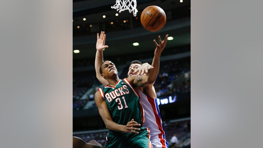 Milwaukee Bucks power forward John Henson (31) is fouled by Detroit Pistons power forward Josh Harrellson (55) in the first quarter of an NBA basketball game in Auburn Hills, Mich., Monday, Nov. 25, 2013. (AP Photo/Paul Sancya)