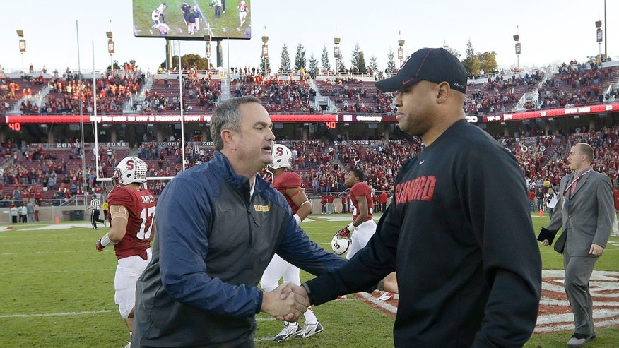 California head coach Sonny Dykes, left, shakes hands with Stanford head coach David Shaw after the Stanford 65-13 victory in an NCAA college football game in Stanford, Calif., Saturday, Nov. 23, 2013. (AP Photo/Tony Avelar)