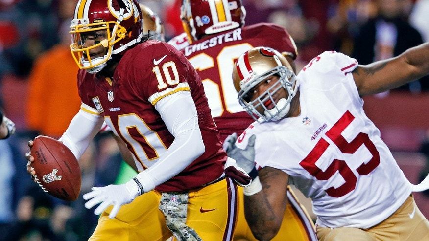 Washington Redskins quarterback Robert Griffin III scrambles away from San Francisco 49ers outside linebacker Ahmad Brooks during the first half of an NFL football game in Landover, Md., Monday, Nov. 25, 2013. (AP Photo/Alex Brandon)