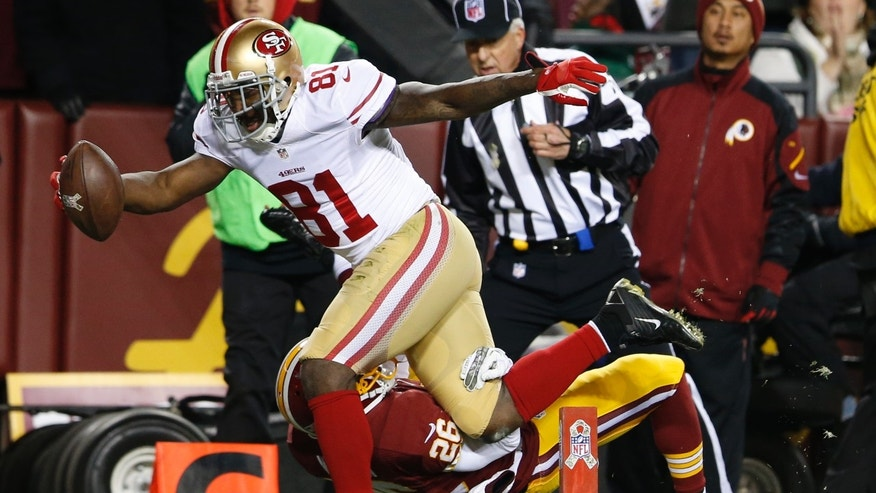 San Francisco 49ers wide receiver Anquan Boldin lands in the end zone with a touchdown pass as Washington Redskins cornerback Josh Wilson hits the turf during the first half of an NFL football game in Landover, Md., Monday, Nov. 25, 2013. (AP Photo/Evan Vucci)