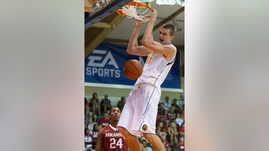 California forward David Kravish dunks in front of Arkansas guard Michael Qualls during the first half of an NCAA college basketball game at the Maui Invitational basketball tournament Monday, Nov. 25, 2013, in Lahaina, Hawaii. (AP Photo/Eugene Tanner)