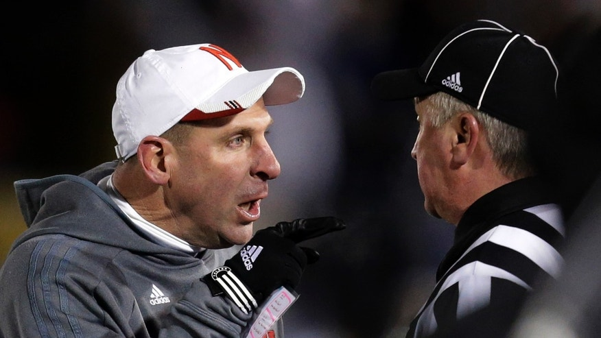 Nebraska head coach Bo Pelini, left, makes his point to an official after having a fourth-quarter touchdown called back during an NCAA college football game against Penn State in State College, Pa., Saturday, Nov. 23, 2013. Nebraska  won 23-20 in overtime. (AP Photo/Gene J. Puskar)