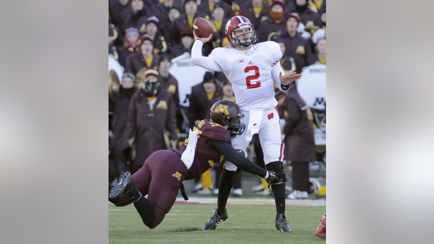 Wisconsin quarterback Joel Stave (2)  passes under pressure from Minnesota defensive lineman Michael Amaefula (98) during the second quarter of an NCAA college football game in Minneapolis Saturday, Nov. 23, 2013. (AP Photo/Ann Heisenfelt)