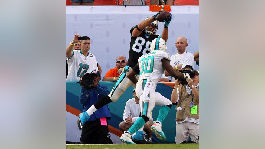 Carolina Panthers tight end Greg Olsen (88) catches a 1-yard touchdown pass over Miami Dolphins' Chris Clemons (30) during the second half of an NFL football game on Sunday, Nov. 24, 2013, in Miami Gardens, Fla. The Panthers defeated the Dolphins 20-16. (AP Photo/The Miami Herald, Charles Trainor Jr.) MAGAZINES OUT